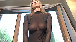 Astonishing blonde with big, firm tits is wearing a black, sheer costume while using a Sybian